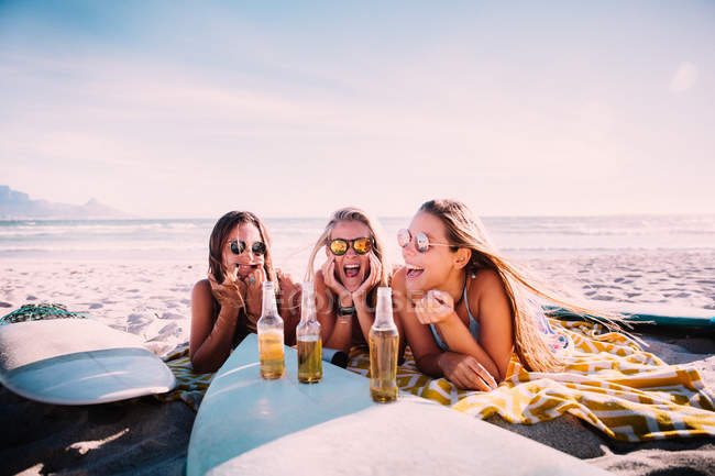 Young adult girls drinking beer at beach and having fun — Stock Photo