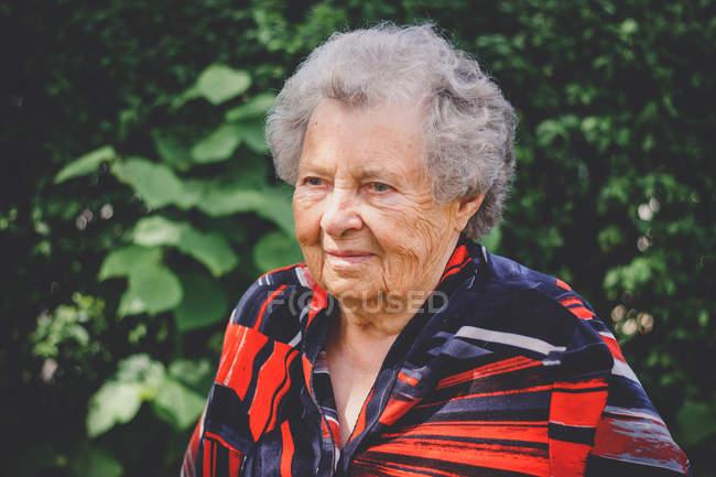 Ritratti di signora anziana con colorato rosso camicetta in piedi all'aperto alle foglie verdi — Foto stock