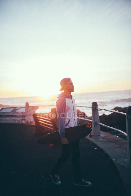 Young man holding longboard at beach during sunset — Stock Photo
