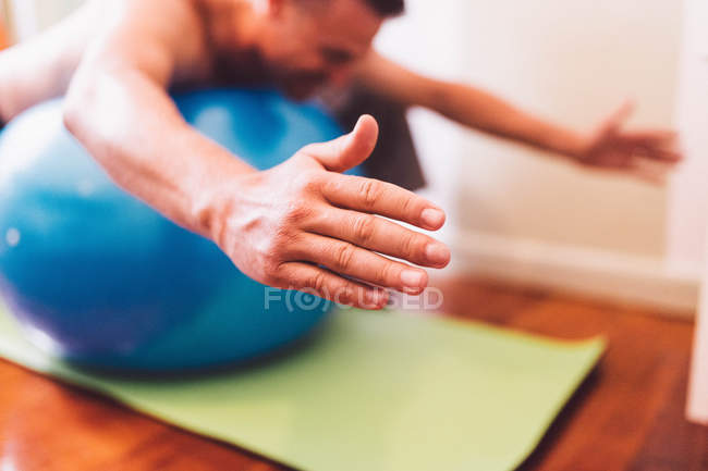 Man balancing on exercise ball at home — Stock Photo