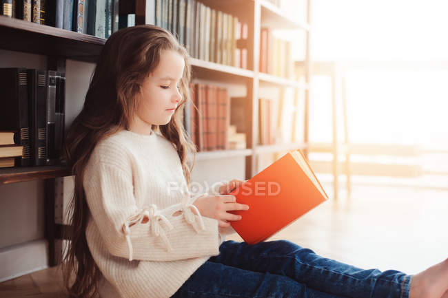 Adorable smart young girl reading book and sitting on floor at book shelves — Stock Photo