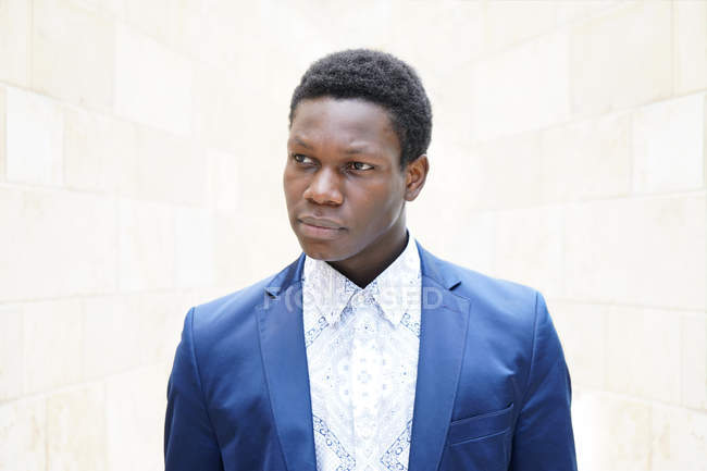 Handsome african man in blue suit jacket posing and looking away — Stock Photo