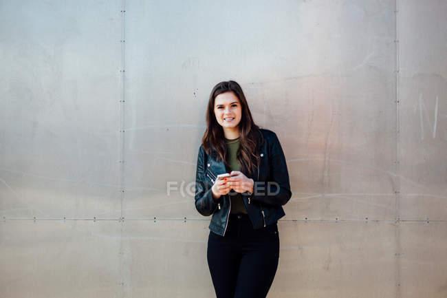 Повна довжина щасливі молода жінка стоїть за смарт-телефону — стокове фото