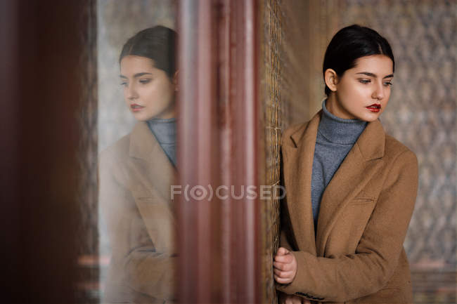 Woman in brown warm coat posing at room wall, glass window with reflection — Stock Photo