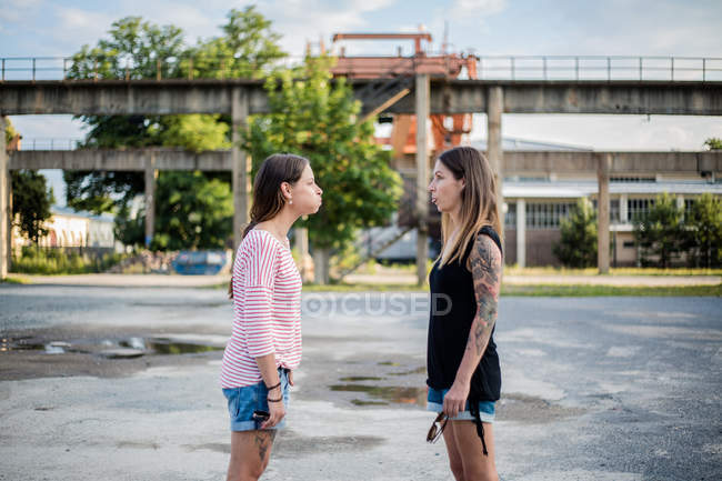 Two women standing outdoors together and making funny facial expression — Stock Photo