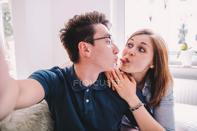 Loving couple enjoying time together and making funny faces, showing tongue — Stock Photo