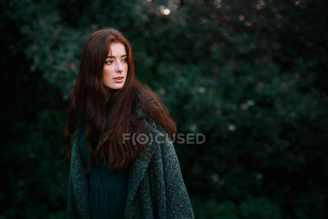 Redheaded caucasian woman with long hair posing in nature with green leaves on background — Stock Photo