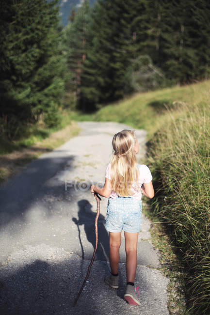 Rear view of young blonde girl holding stick and walking in countryside path — Stock Photo