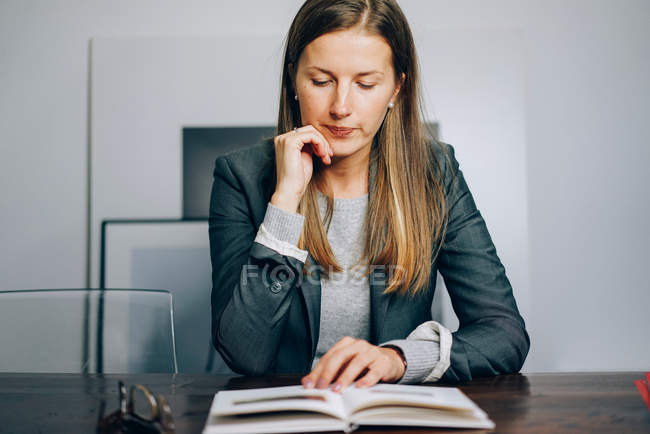 Business woman sitting at desk and reading book — Stock Photo