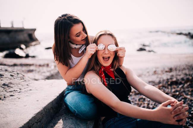 Due ragazze felici sulla spiaggia dal mare divertendosi con le conchiglie — Foto stock