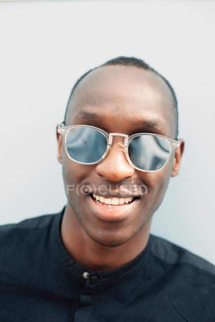 Smiling casual young black man wearing sunglasses — Stock Photo
