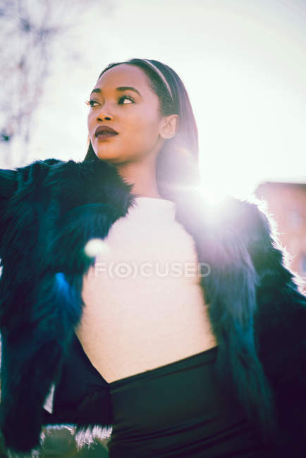 Young stylish African woman in fur coat, lens flare — Stock Photo
