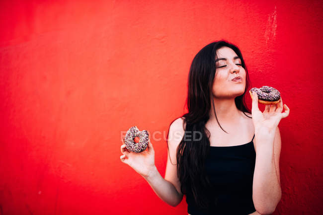 Jovem mulher comendo donuts de chocolate contra o fundo vermelho — Fotografia de Stock