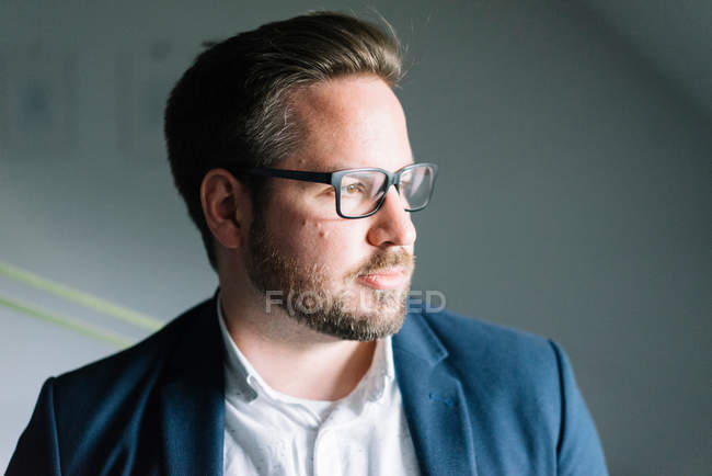 Portrait of a bearded man wearing eyeglasses and looking away — Stock Photo