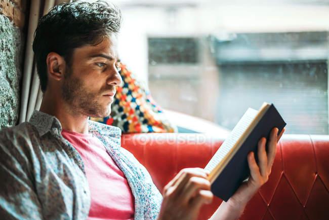 Mann, Buch lesen und sitzen am Fenster — Stockfoto