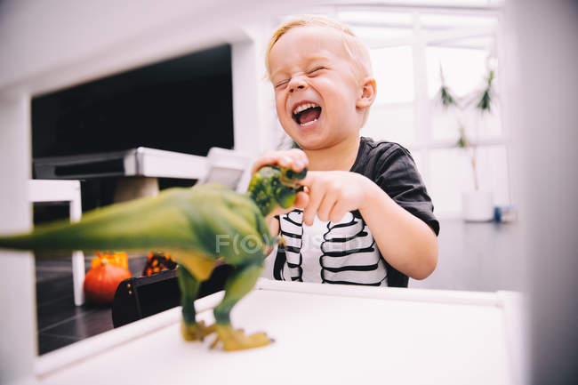 Little boy playing with dinosaur toy — Stock Photo