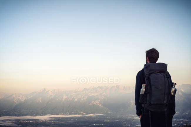 Rear view of a man overlooking the mountains — Stock Photo