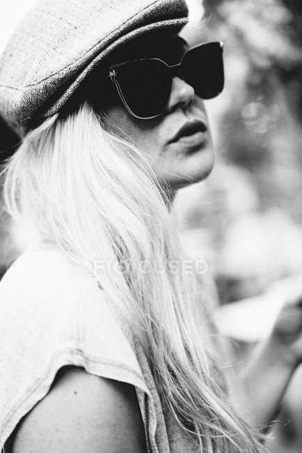 Fashion portrait of a young woman wearing a hat and glasses — Stock Photo
