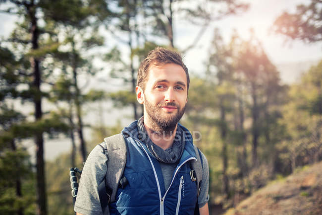 Portrait of young man in forest looking at camera — Stock Photo