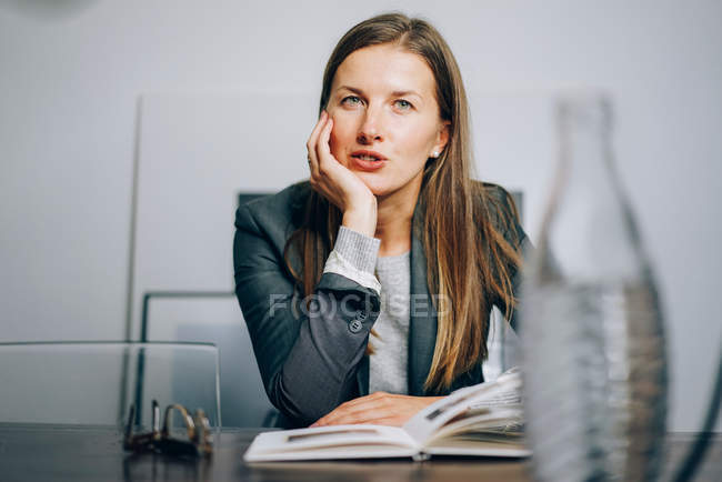 Teacher woman sitting at desk with book and looking at camera — Stock Photo
