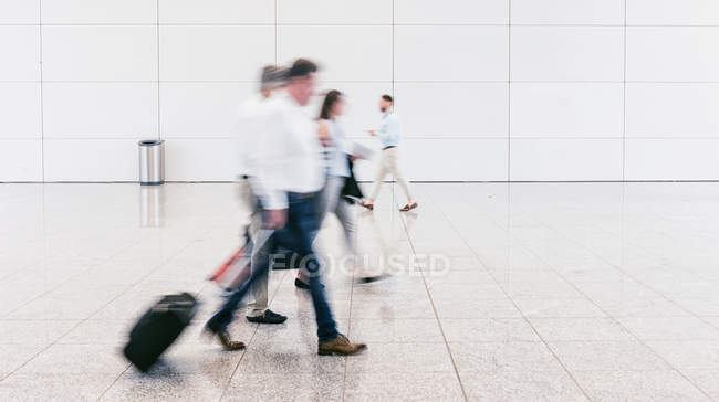 Blurred motion of groups of people walking on airport — Stock Photo