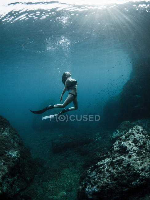 Donna che nuota sott'acqua in pinne, foto subacquea di acqua di mare blu profondo — Foto stock