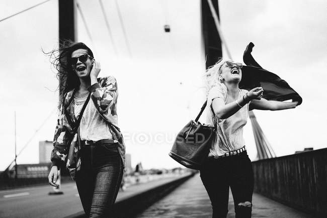 Two girls best friends walking on bridge and laughing — Stock Photo