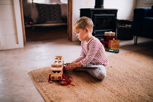 Ragazzo prescolare che gioca con auto giocattolo sul tappeto in camera piano — Foto stock