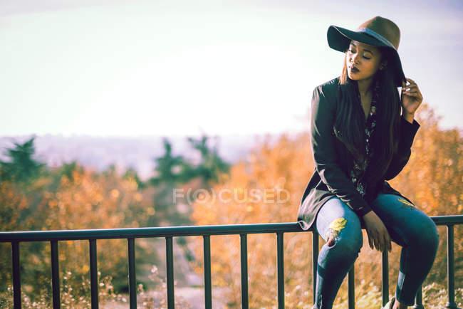 Donna africana in cappello guardando verso il basso e che si siede sulla rete fissa — Foto stock