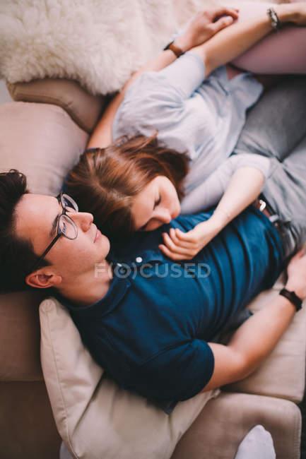 Casal alegre, apreciando o tempo juntos no sofá — Fotografia de Stock
