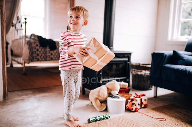 Süsser Boy mit Weihnachtsgeschenke zu Hause spielen und tragen pyjama — Stockfoto