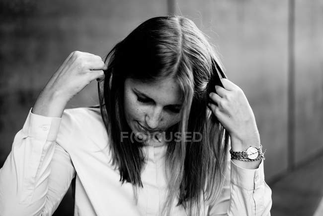 Caucasian woman adjusting her hair, black and white photo — Stock Photo