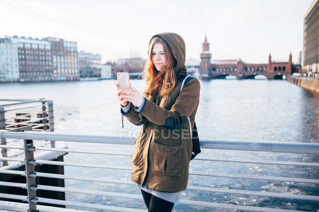 Full length of young woman using phone over  river — Stock Photo