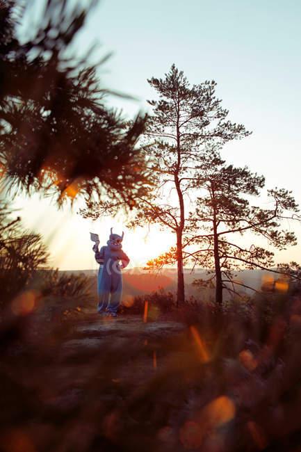 Costume mostro blu da portare di persona e in piedi nelle montagne al tramonto con l'ascia — Foto stock