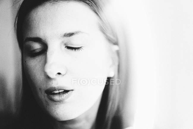 Portrait of young woman with closed eyes, black and white photo — Stock Photo