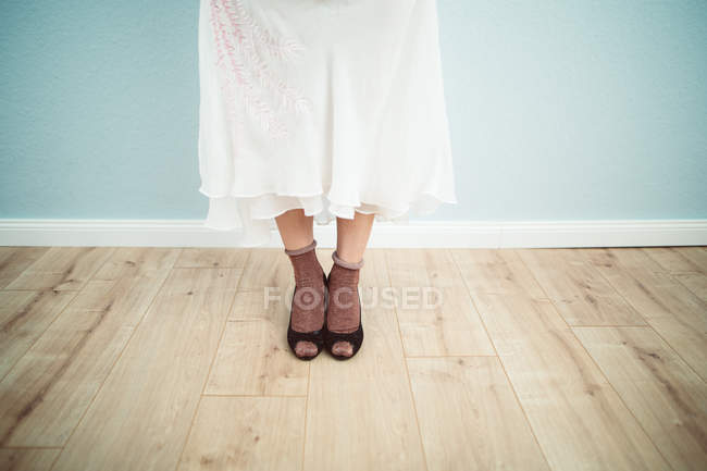 Low section shot of female legs in shoes, woman standing in white skirt — Stock Photo
