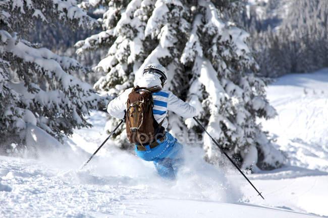 Homem de esquiador nas montanhas cobertas com árvores, férias de inverno — Fotografia de Stock