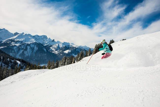 Mujer esquiadora de esquí en las montañas cubiertas de nieve, vacaciones de invierno - foto de stock