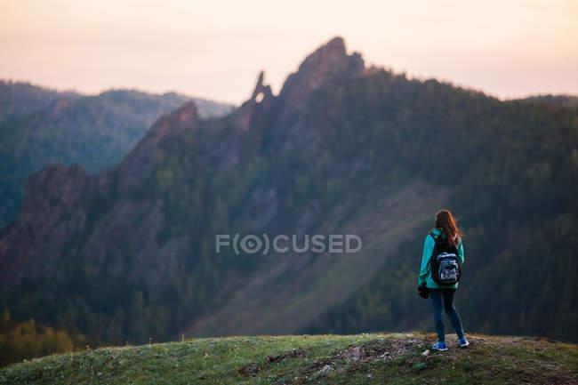 Donna di viaggiatore in piedi nelle montagne — Foto stock