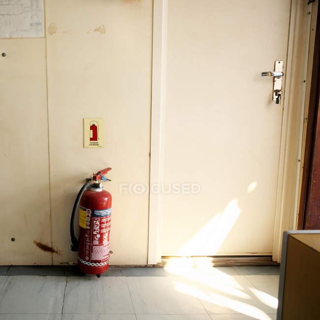 Красный огнетушитель в комнате на этаже — стоковое фото