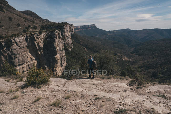 Rear view of man standing on rocky mountain against clear sky — Stock Photo