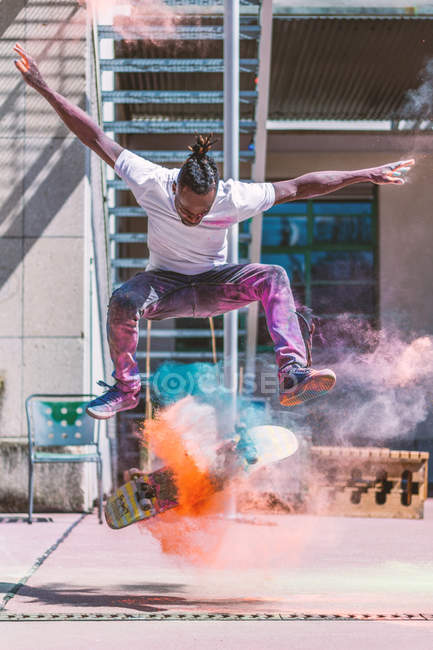Action shot of man jumping on a skate board in colorful powder paint — Stockfoto