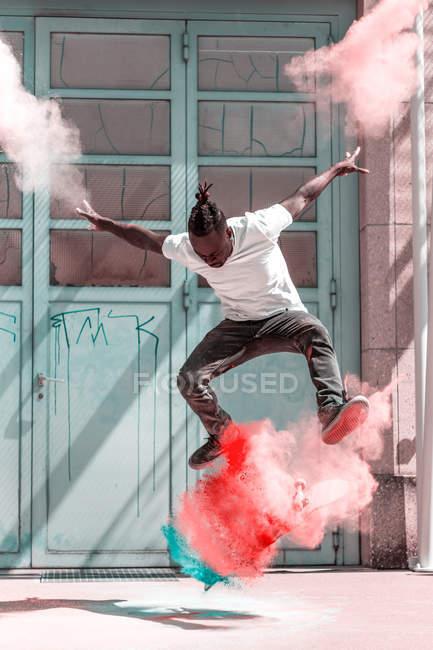 Mann, springen in der Luft über Skateboard mit bunten Pulverlack — Stockfoto