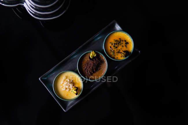 Vista superior de tres tazones con deliciosos postres y flores comestibles en bandeja sobre fondo negro. - foto de stock
