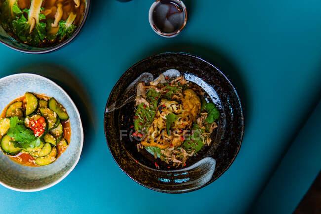 Vue du dessus de la nourriture de style asiatique, délicieux plats orientaux dans des bols sur fond bleu — Photo de stock