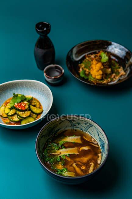 Délicieux plats orientaux dans des bols sur fond bleu, nourriture de style asiatique — Photo de stock