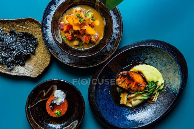 Vista superior de conjunto de deliciosos platos, pescado y caviar rojo servido en platos sobre fondo azul - foto de stock