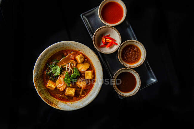 Top view of delicious soup and bowls with ingredients and sauces on black background — Stock Photo
