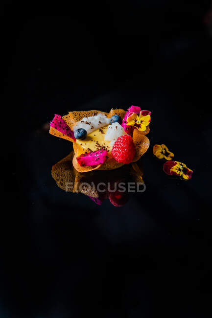 Close-up view of delicious dessert with berries and edible flowers on black background — Stock Photo
