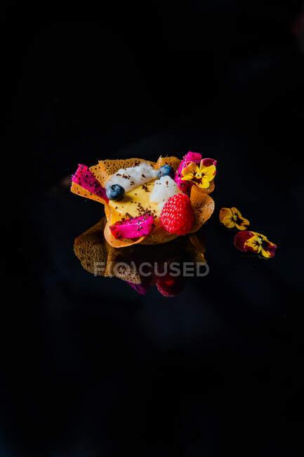 Крупным планом восхитительный десерт с ягодами и съедобными цветами на чёрном фоне — стоковое фото